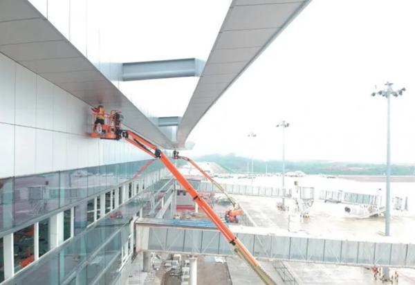 玉林福绵机场工人利用升降机装修航站楼外墙